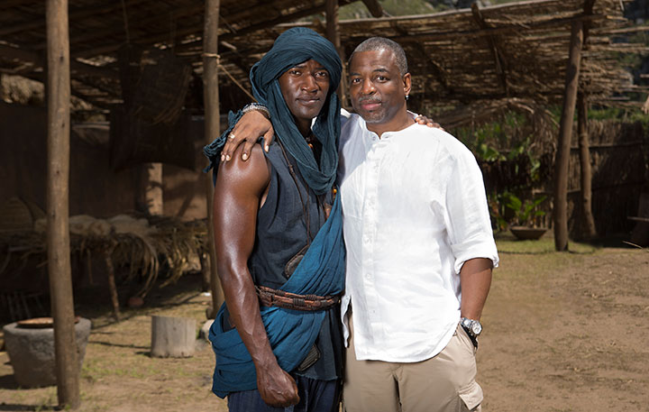 Malachi Kirby on set as Kunta Kinte alongside exec producer LeVar Burton, who played the same character in the original series